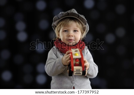 little toddler playing with wooden cars, on black background - stock photo