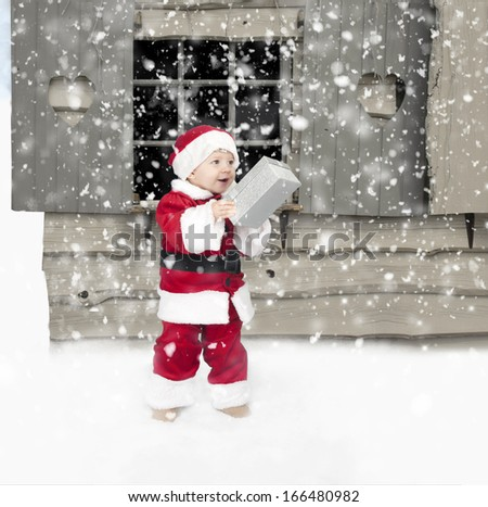 little toddler santa claus with christmas present outdoors in the snow