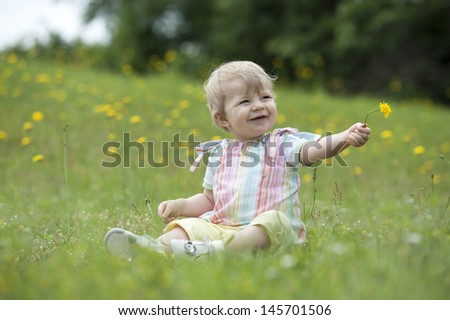 little toddler seated in the garden , playing with flowers - stock photo