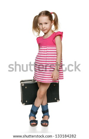 Little tourist. Little girl with old fashioned suitcase in full length standing over white background - stock photo