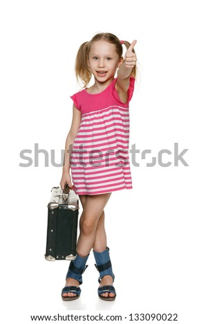 Little tourist. Little girl with old fashioned suitcase showing thumb up sign - stock photo