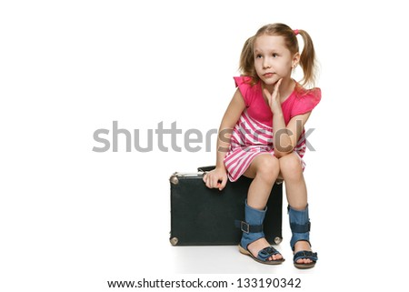 Little tourist. Little girl with sitting on the old fashioned suitcase in full length looking away at blank space for your text, over white background - stock photo