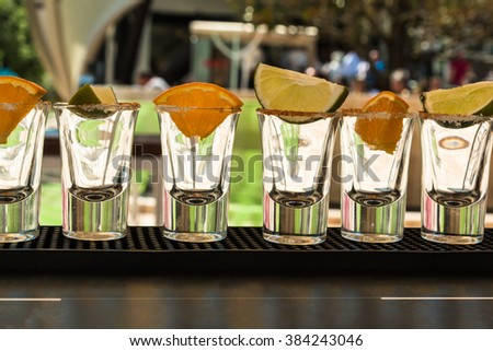 Little Transparent Glasses in Line with Orange and Lime Slices Ready to Tequila Shots - stock photo
