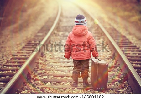 little traveler with a suitcase on the railroad - stock photo
