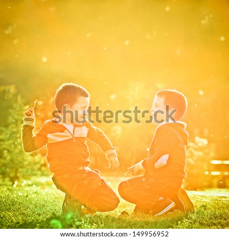Little twin brothers having fun in the park in a beautiful sunset. - stock photo