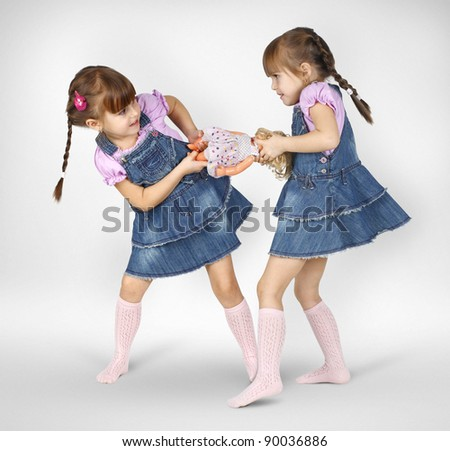 little twin girls fighting and shared doll - stock photo