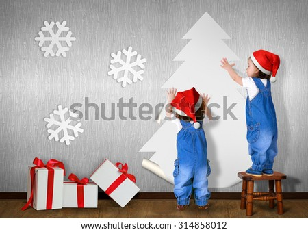 Little twins dressed Santa hat, glue Christmas tree on wall at home, xmas concept - stock photo