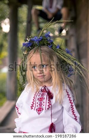 Little Ukrainian girl in the coronet from flowers - stock photo