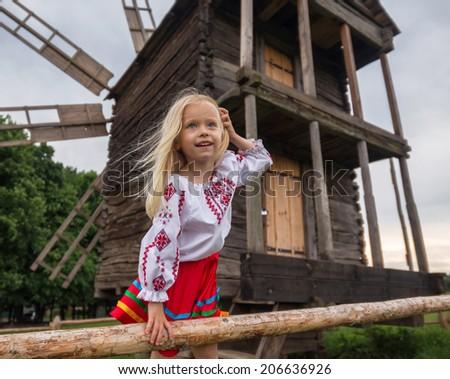 little ukrainian girl smiling on the hedge near old wooden mill  - stock photo