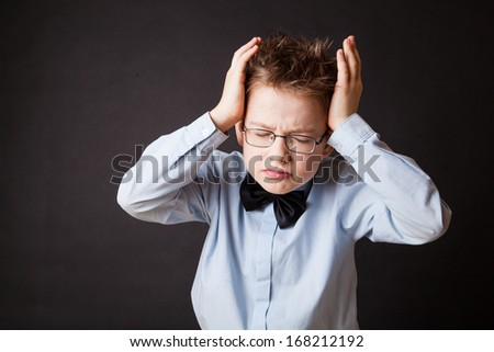 Little unhappy boy holding his head over the black - stock photo