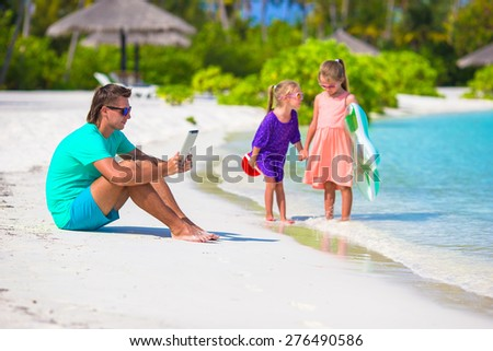Little upset sad girls waiting father to swim while he working - stock photo