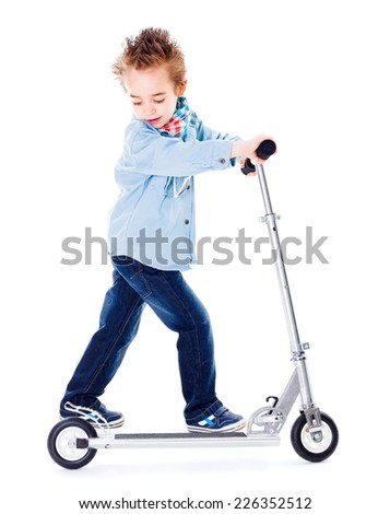 Little urban boy playing with scooter - stock photo