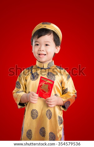 Little Vietnamese boy holding red envelops for Tet. The word mean double happiness. It is the gift in lunar new year or Tet Holiday on red isolate background..