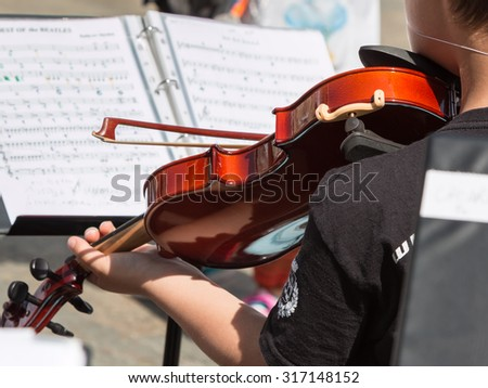 Little Violinist with white Hat during Outdoor Concert, Music Sheet in Background - stock photo