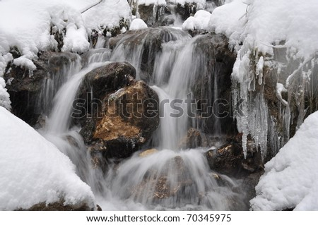 Little waterfall and needle ice in the mountain - stock photo
