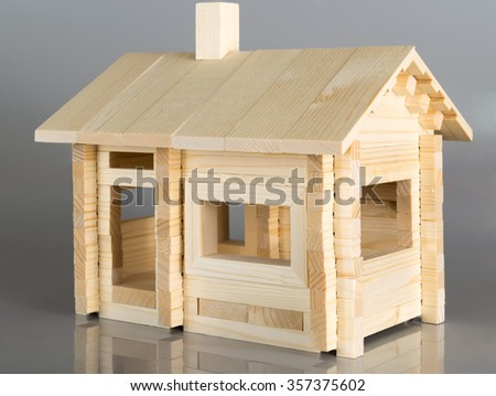Little weekend house with natural colored toy on gray background