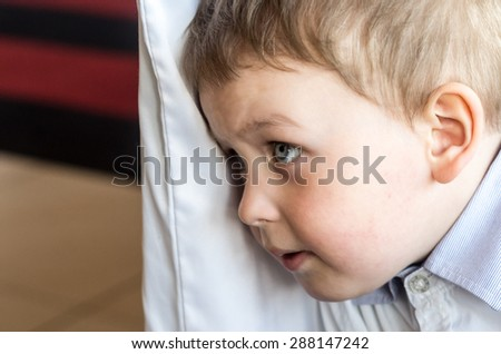 little white boy looks concerned ahead - stock photo