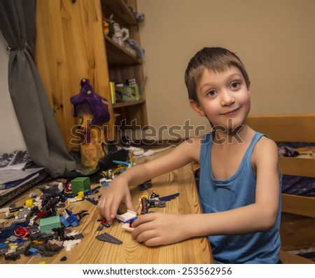 Little white boy smiling, interesting, holding a colorful Lego,  in the house, in his room - stock photo