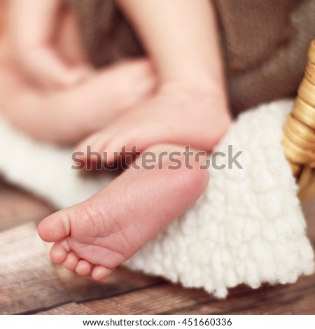Little white feet of a newborn baby who sleeps in a basket on a white blanket - stock photo