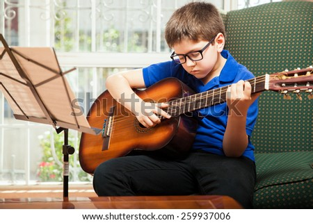 Little white kid with glasses practicing some new guitar chords at home - stock photo