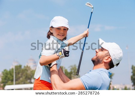 Little winner. Cheerful young man picking up his son while standing on the golf course - stock photo