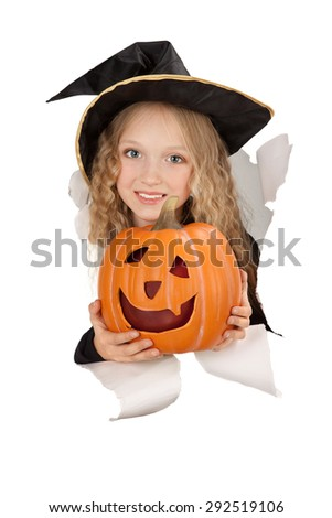 Little witch in a black hat with web and spider with a pumpkin looking out of the paper in the hole