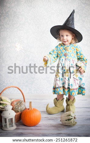 Little witch in black hat with pumpkin - stock photo