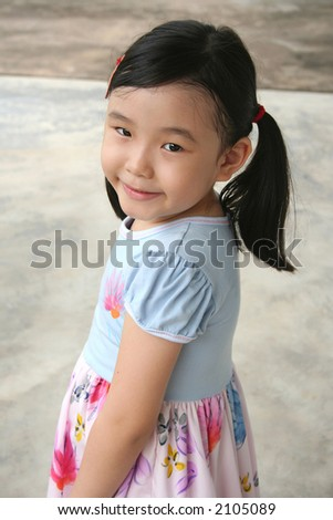 Little with pony-tail standing  and smiling happily - stock photo