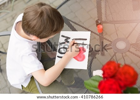 "Little 7 year old boy paints greeting card for Mom on Mother's Day with the inscription ""I love you mom"". Outdoors. Mother's Day - stock photo"
