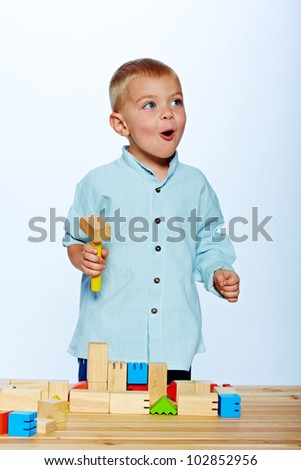 little 3 year old toddler boy playing with bright wooden blocks on a wooden table over light blue studio background
