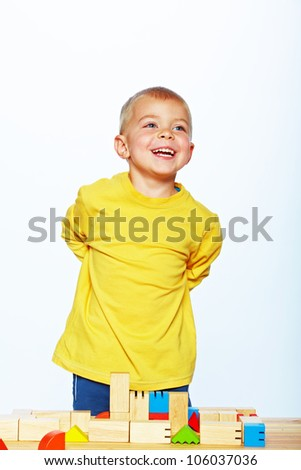 little 3 year old toddler boy playing with bright wooden blocks on a wooden table over white background. - stock photo