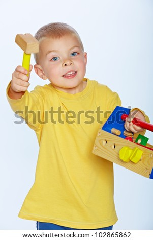little 3 year old toddler boy with a wooden hammer and toolbox over studio background - stock photo
