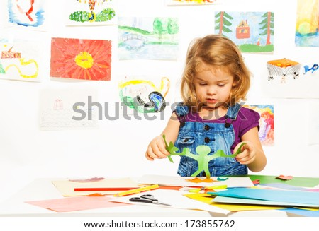 Little 3 years old blond girl gluing color cardboard holding cut out paper garland  - stock photo