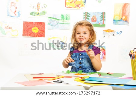 Little 3 years old blond girl gluing color cardboard smiling and looking at camera - stock photo