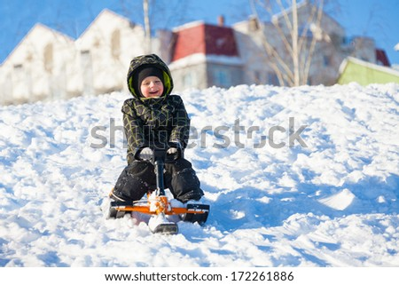 Little 3 years old boy sliding on the sledge scooter on winter day - stock photo