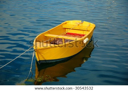 little yellow boat at rope mooring - stock photo