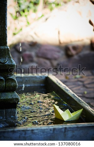 Little yellow origami paper boat in a small outdoor water fountain - stock photo