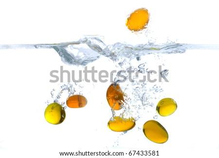 Little yellow stones splash in water - stock photo