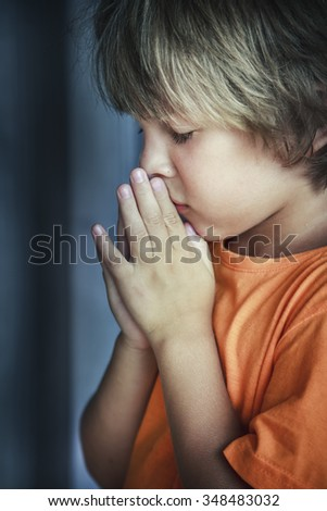 Little young beautiful boy spiritual peaceful praying and wishing - stock photo
