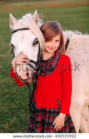 Little young girl child hugging a white pony at his head and smiling Outdoors - stock photo