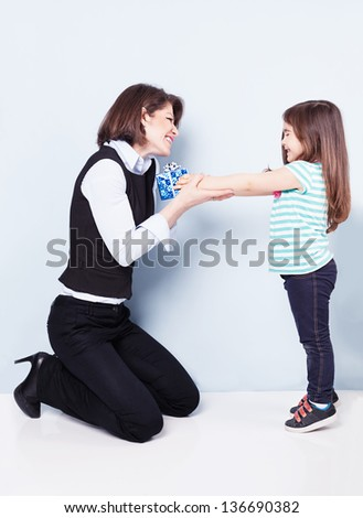 littler cute girl giving her mom a present on blue background - stock photo