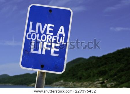Live a Colorful Life sign with a beach on background - stock photo