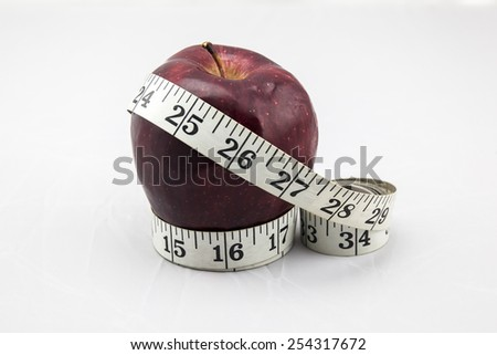 Live a Healthy Life - Red Apple with Measure Tape on Isolated White Background - stock photo