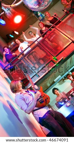 Live performance of a guitarist in a nightclub - stock photo