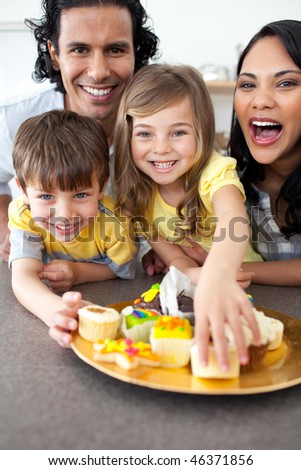 Lively family eating cookies  in the kitchen
