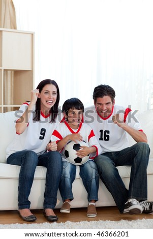 Lively family watching football match on television