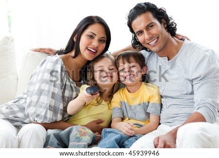 Lively family watching TV  together sitting on a sofa