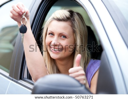 Lively female driver showing a key with a thumb up after buying a new car - stock photo