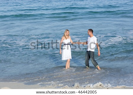 Lively lovers having fun together at the seaside