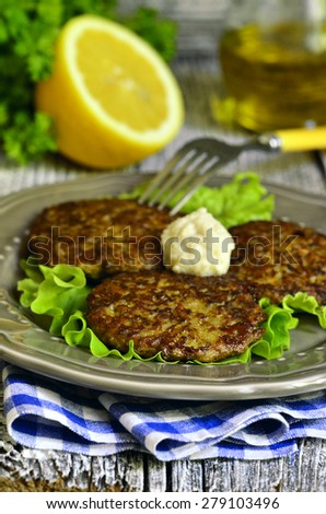 Liver and rice fritters with vegetables and cheese on a rustic background. - stock photo